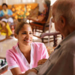 Healthcare Provider Helping Elderly Man On Wheelchair